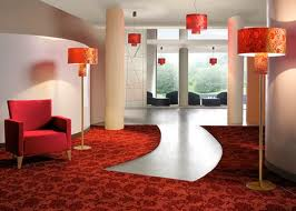 A fancy building lobby with reddish furniture and lamps