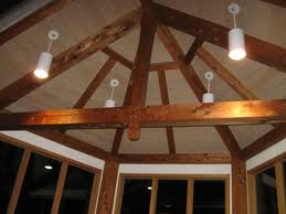 An image of a room ceiling with white hanging lamps and wooden support beams