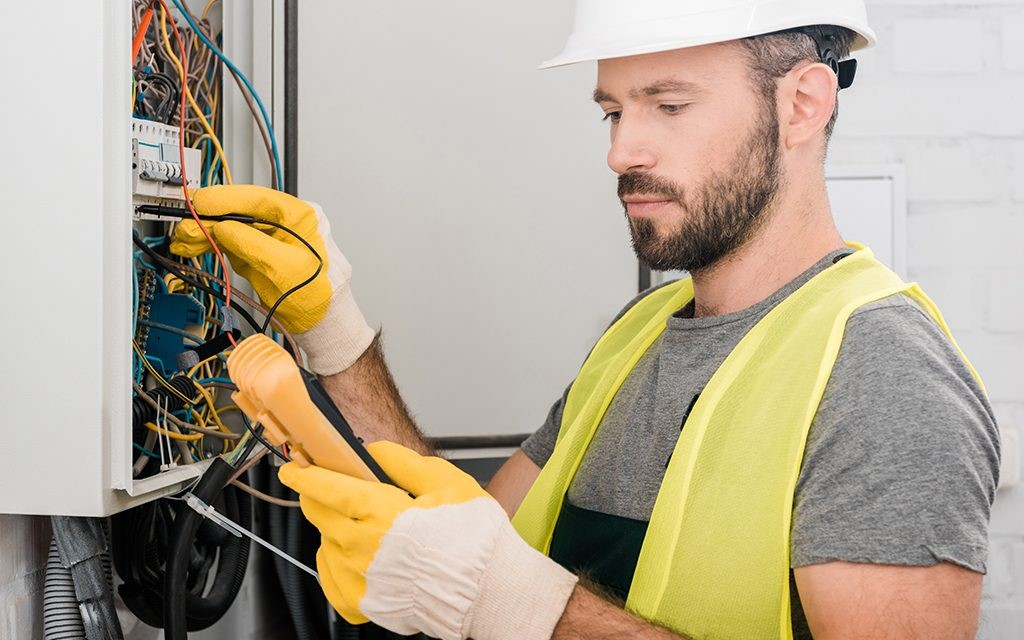 An electrician working on a electrical panel using a voltage tester