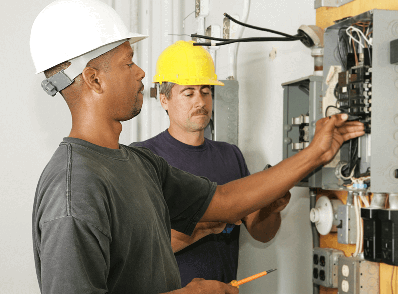 two electricians working on a circuit breaker panel