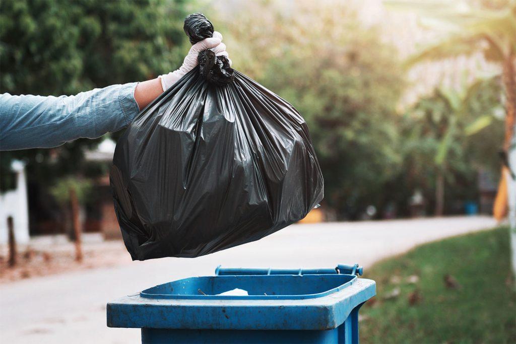 image of garbage bag disposal into waste basket